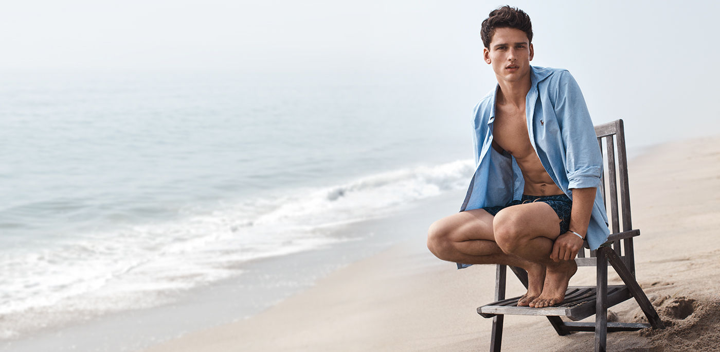 coach outlet online official website i5wj  Man on beach wears unbuttoned blue oxford shirt & swim trunks