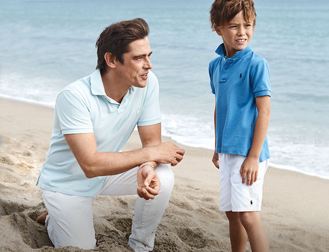 Man on beach in white denim and faded blue Polo shirt