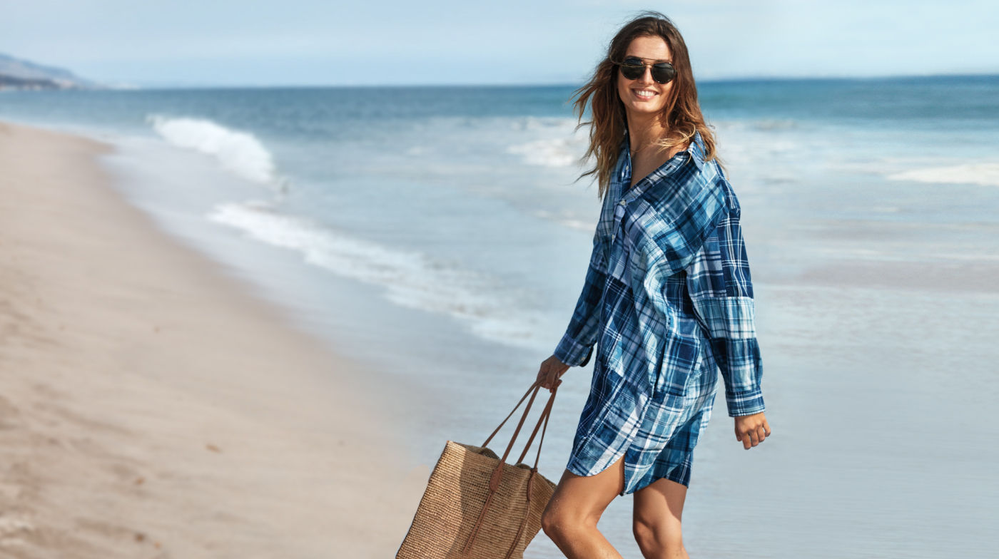 Woman on beach in patchwork shirtdress made from indigo-dyed madras