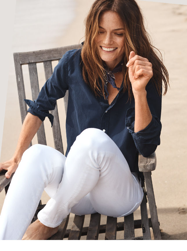 Woman in navy button-down & white jeans sits on beach chair