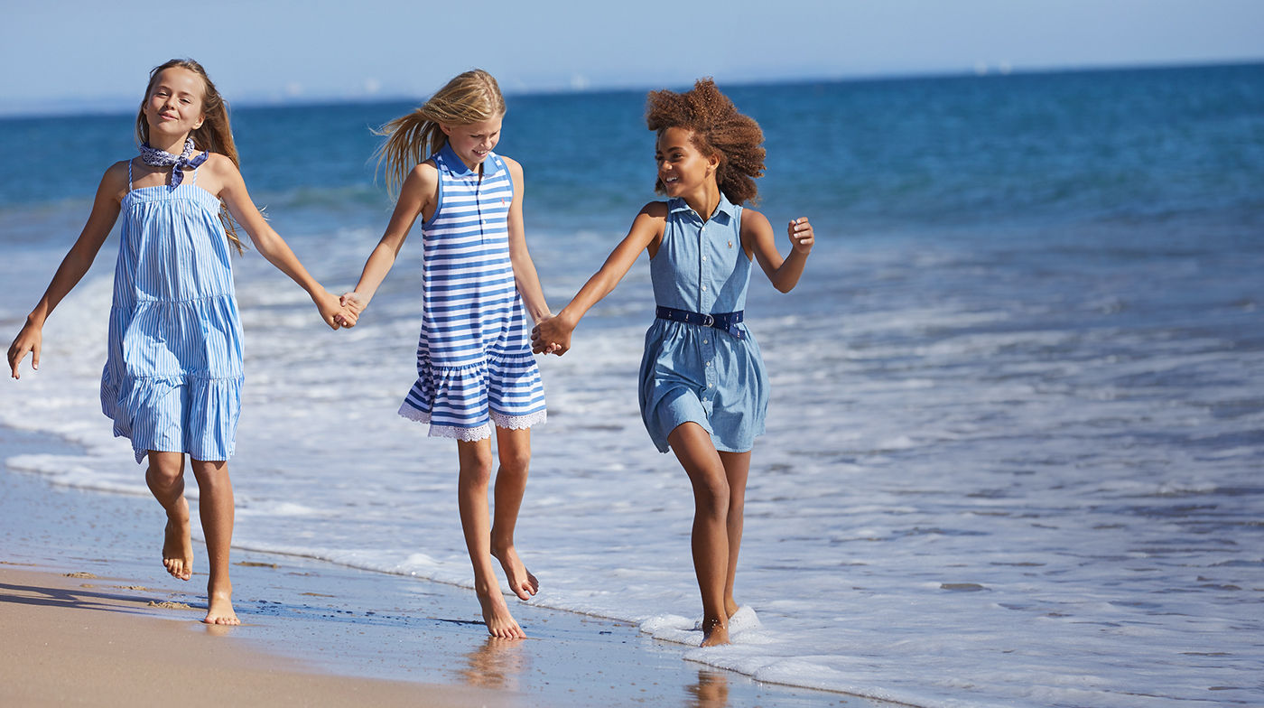 Three girls walk along the water in blue-hued summer dresses