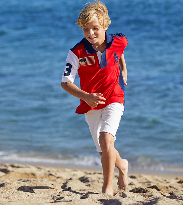 Boy runs on beach in American flag patch Polo shirt