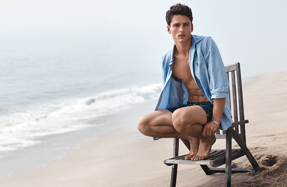 Man on beach wears unbuttoned blue oxford shirt & swim trunks