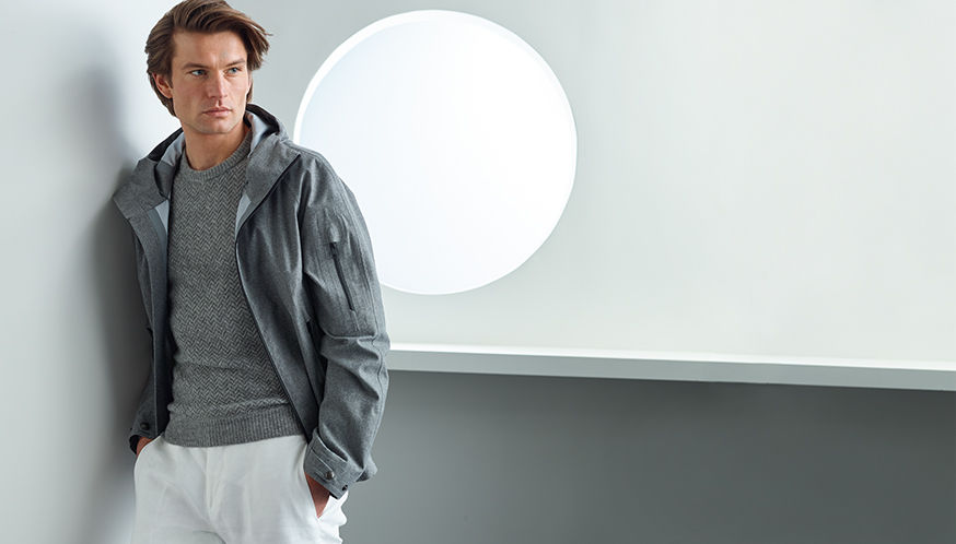Man in grey performance jacket with zip pocket at left sleeve