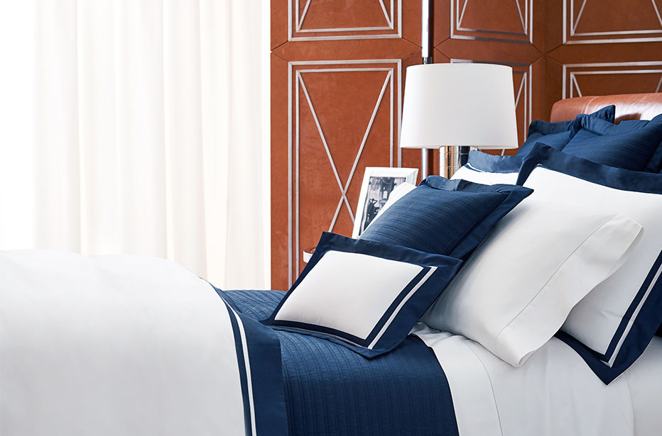 Neatly made bed with crisp white & navy sheets & pillowcases