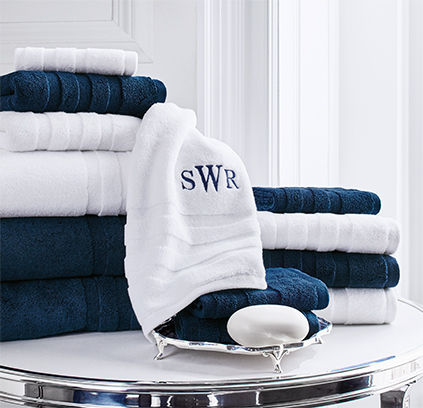 Monogrammed white hand towel next to stack of larger towels