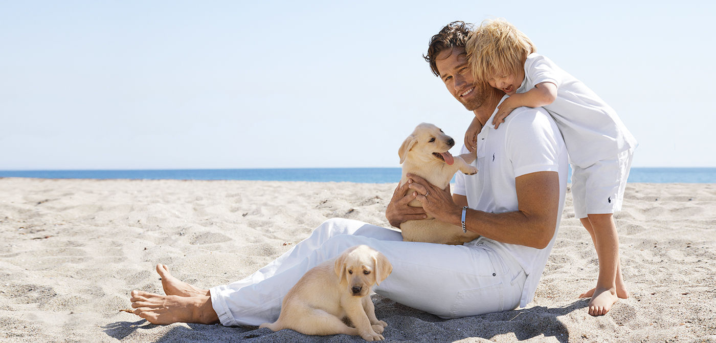Dad & son in matching white Polo shirts on beach with puppies
