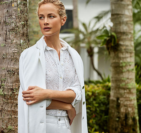 Woman in white eyelet embroidered shirt and matching blazer over shoulders