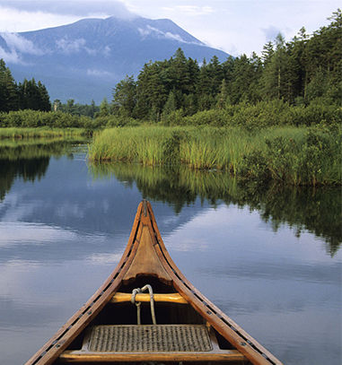 Canoe in water surrounded by green shores & mountains in distance