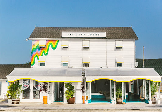 White paneled Surf Lodge with painted rainbow-hued abstract accent