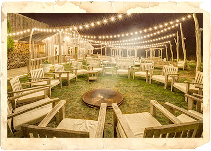 Outdoor lounge area with fire pit, wooden chairs & white string lights
