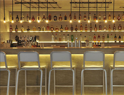 Clean-lined bar area with drop lights and white & silver stools