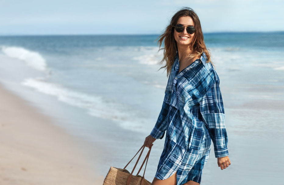 Woman walks on beach in blue madras shirtdress