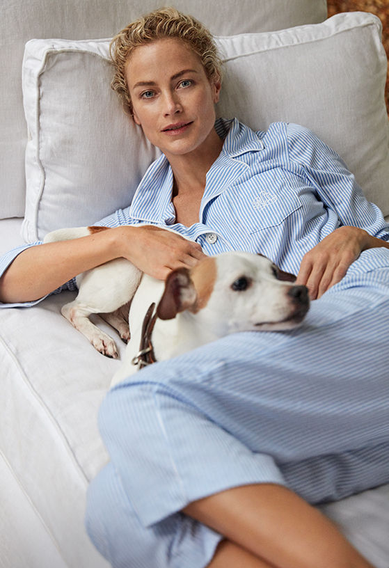 Woman in blue-and-white striped PJs cuddling with dog on couch