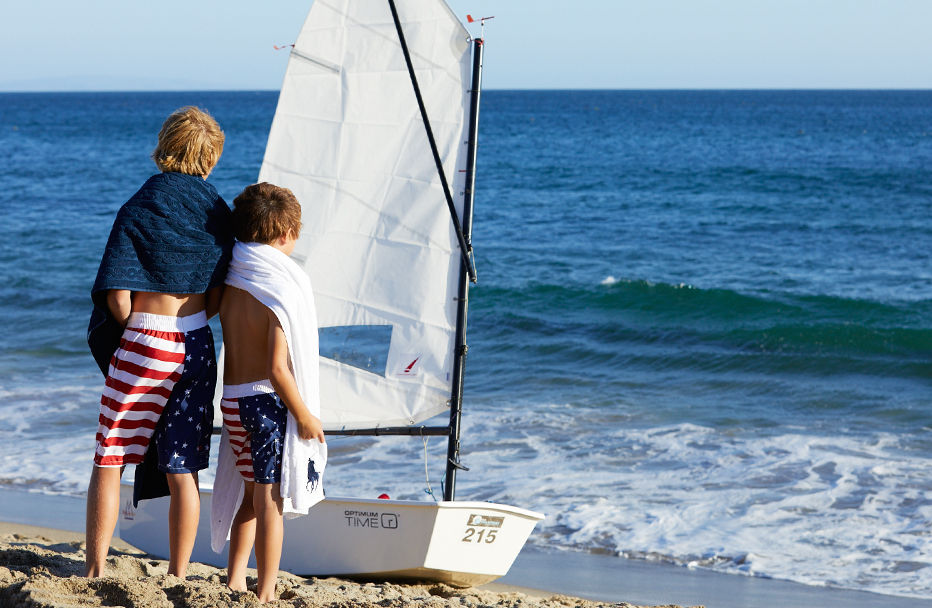 Boys on beach wear matching American flag­–inspired swim trunks.