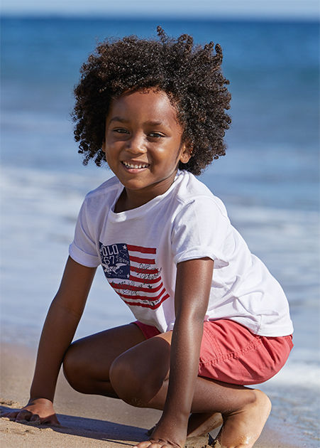 Boy wears American flag­–inspired tee with red shorts.