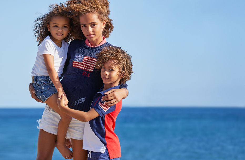 Kids wear patriotic summer outfits in red, white, and blue on beach.