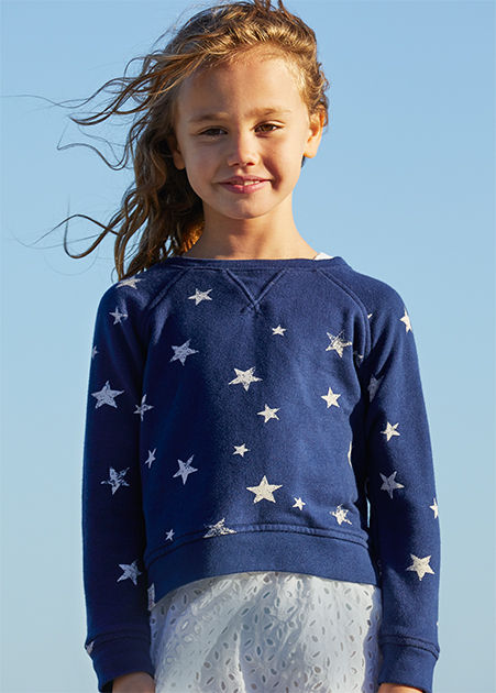Girl wears navy sweatshirt with white stars and a white eyelet skirt.