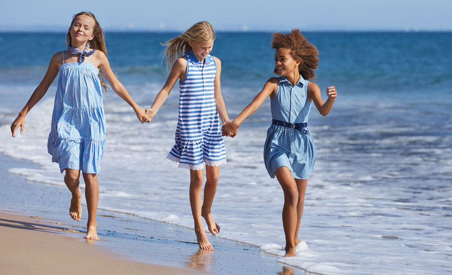 Girls hold hands on beach wearing various blue summer dresses.