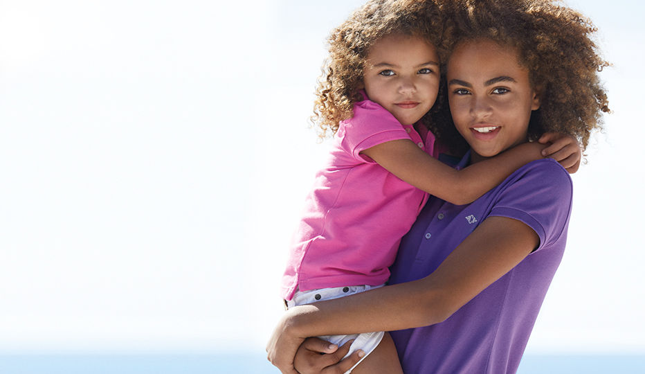 Older girl wearing purple Polo holds younger girl wearing pink Polo.