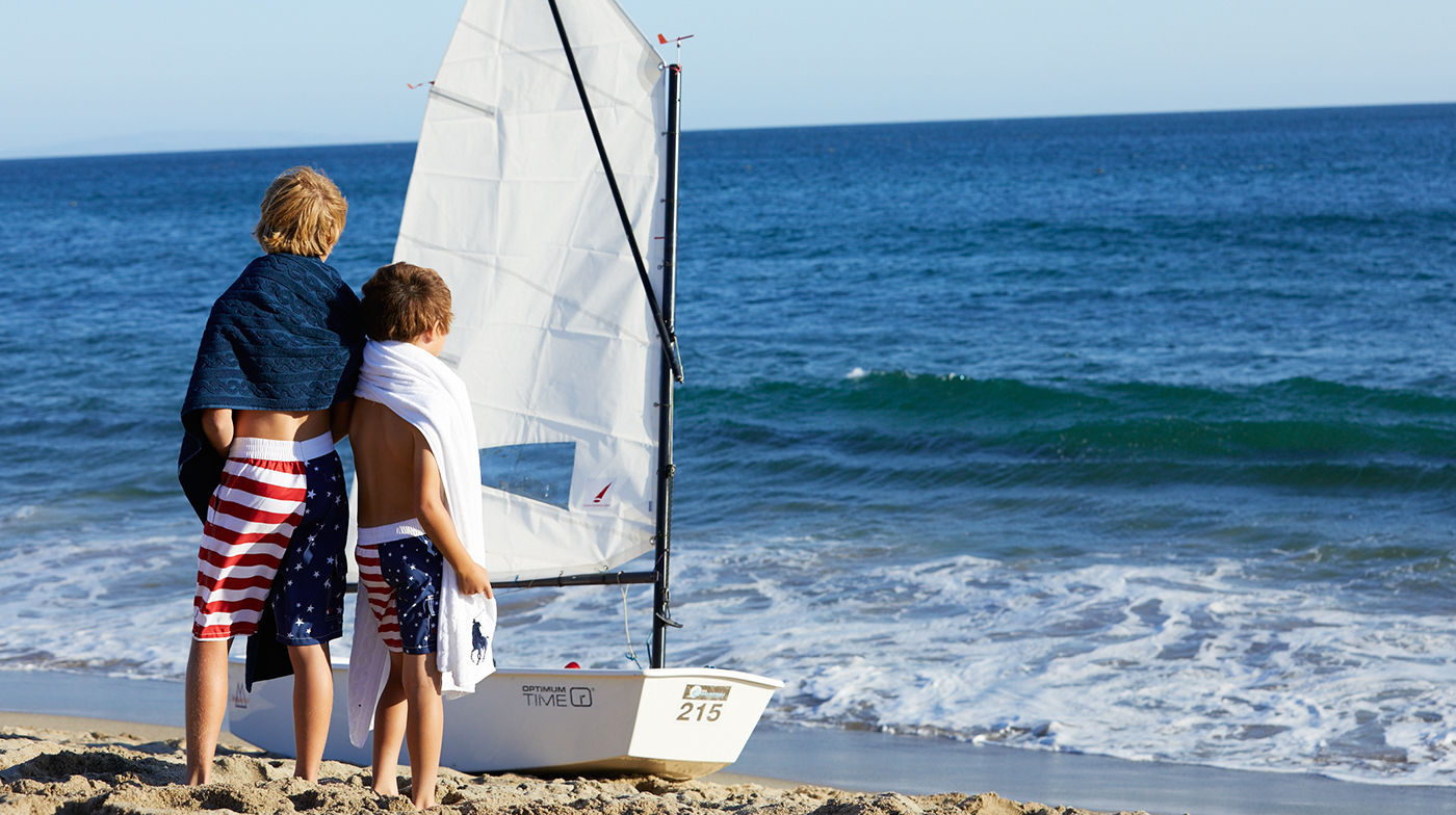 Boys in American flag–inspired swim trunks next to sailboat on beach