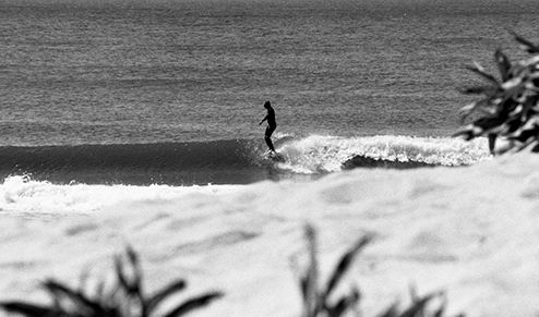 Black & white image of surfer on beach
