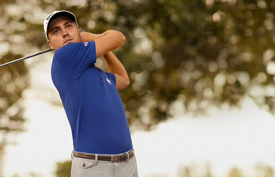 Justin Thomas swings golf club wearing deep blue Polo shirt
