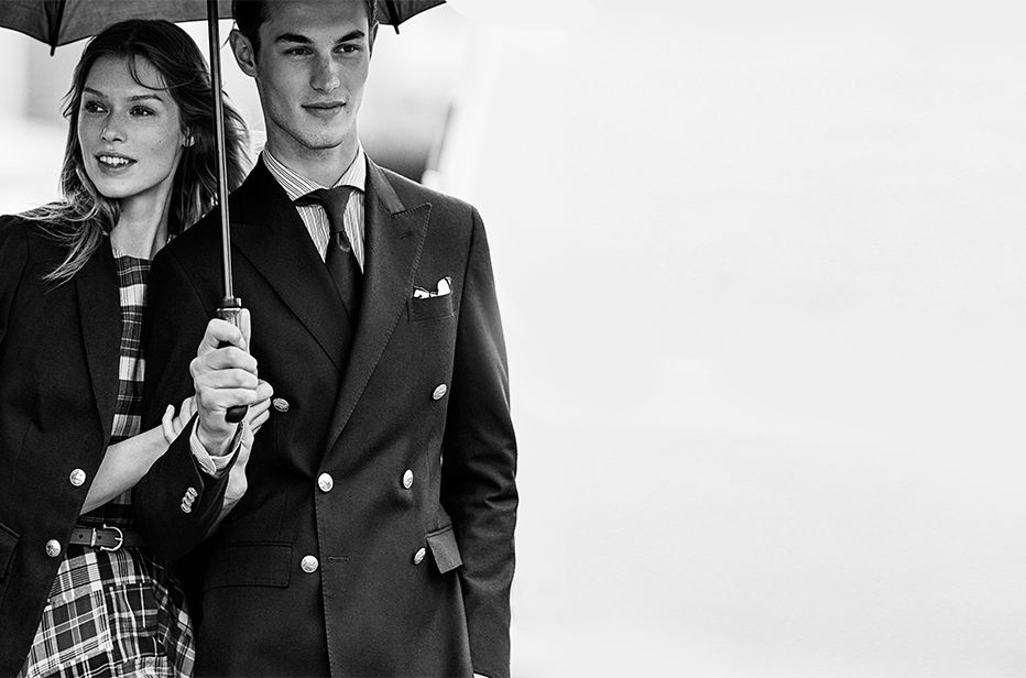 Image of man and woman under umbrella in spectator apparel