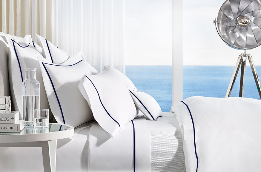 Neatly made bed with navy-trimmed white sheets & pillow covers