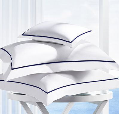 Pile of pillows with white covers and navy trim