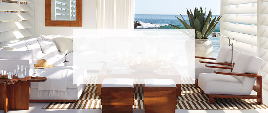 Clean-lined white couch & seats juxtaposed against a graphic striped throw rug