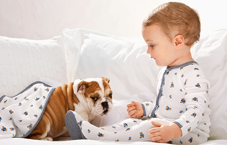 Baby boy wears Polo Bear–patterned one-piece while playing with bulldog puppy.
