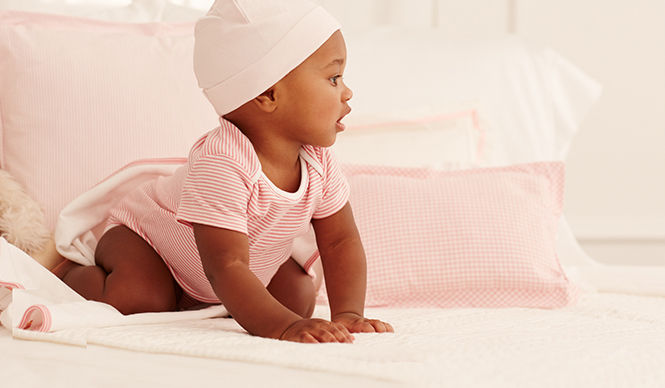 Baby wears pink-and-white striped one-piece with light-pink hat.