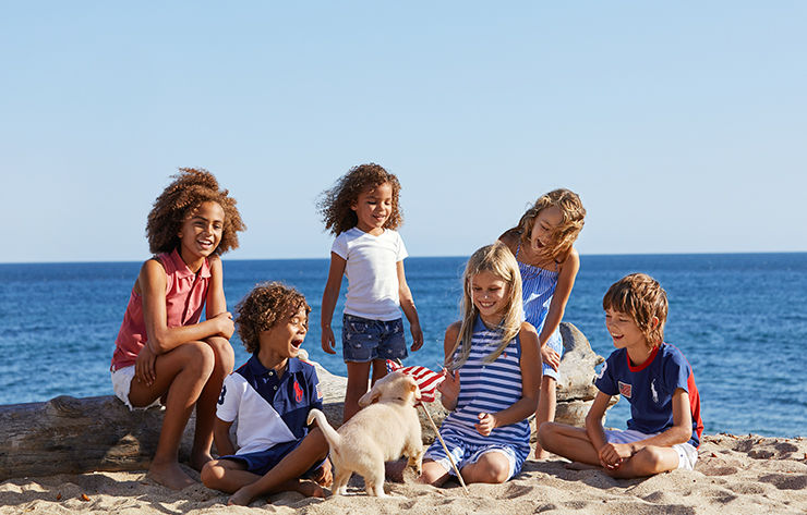 Group of kids in red, white, and blue outfits play on beach.