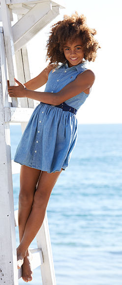 Girl wears sleeveless chambray shirtdress with navy belt.
