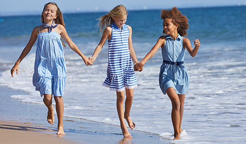 Girls in blue dresses hold hands on beach.