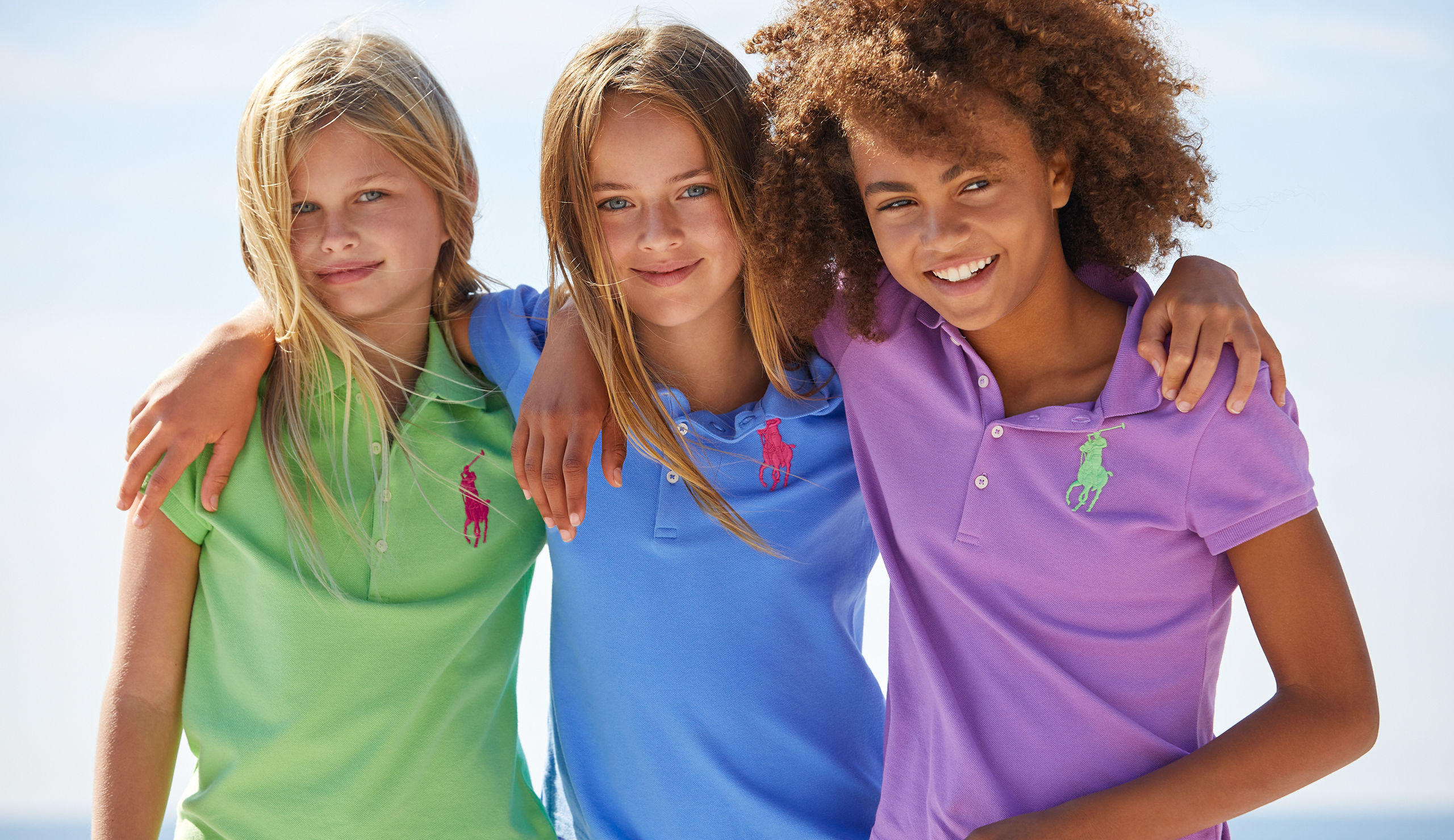 Three girls with arms around each other wearing bright-hued Polo shirts