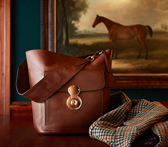 Burnished brown calfskin bag with thick shoulder strap and front flapped pocket