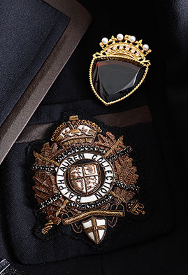 Crown & shield brooches featuring bullion embroidery and jewels