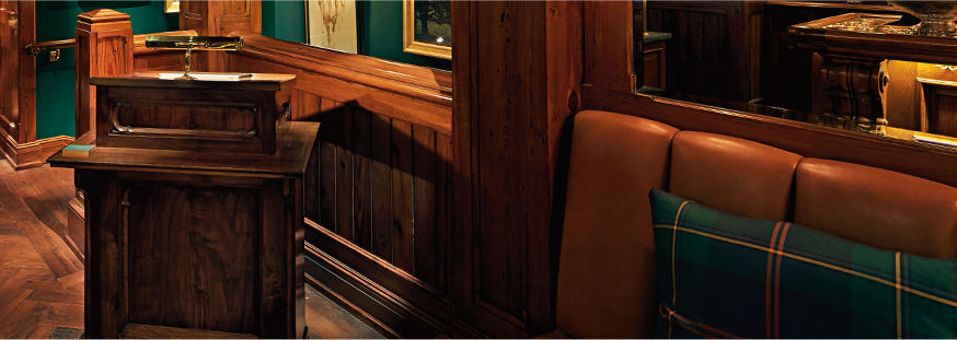 Entrance of the Polo Bar featuring wood paneling & deep-green walls