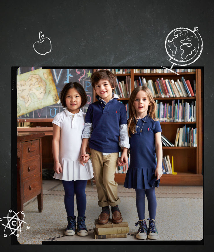 Kids in classroom model Polo shirts and Polo dresses in navy and white.