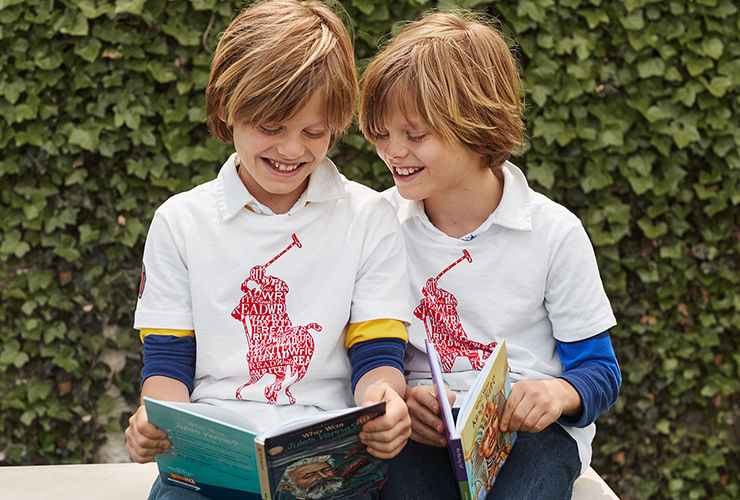Two boys in Polo Literacy tees read books.