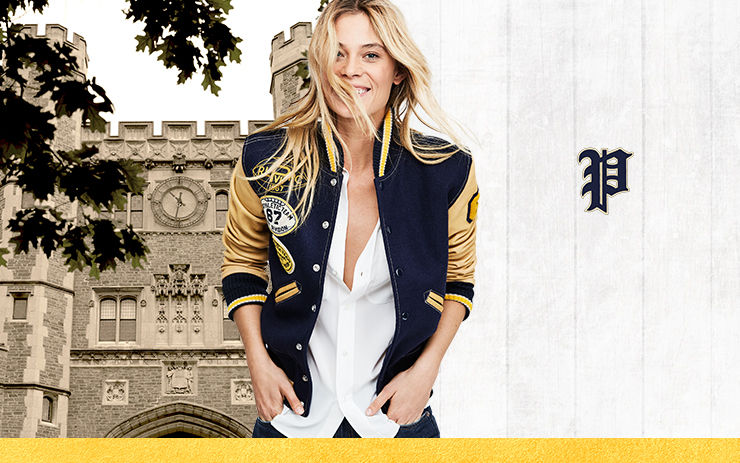 Woman models varsity-inspired jacket over white button-down; collegiate building in background.