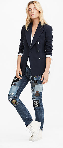 Woman wears navy blazer with ripped-and-repaired jeans.