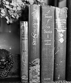 Black and white image of bookshelf with worn books.