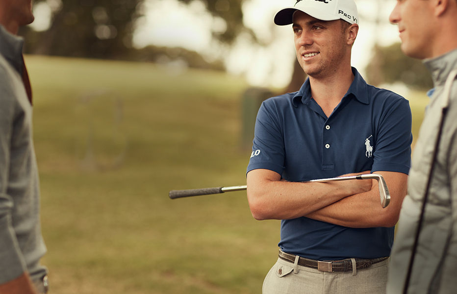 Justin Thomas wears blue Polo and chinos while on golf course.
