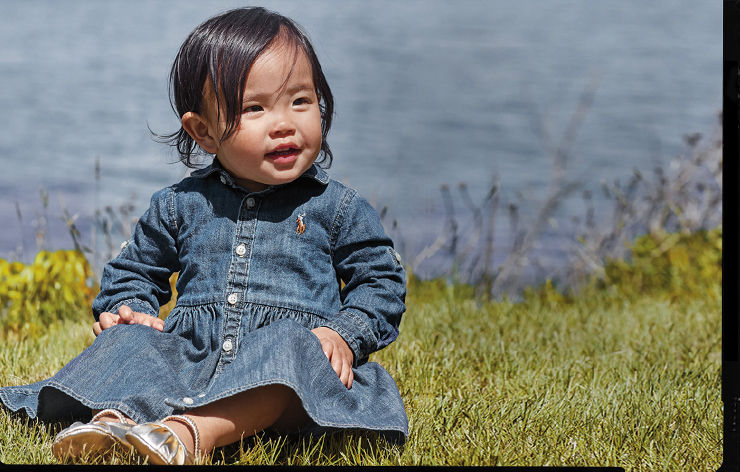 Baby girl wears denim long-sleeve button-down dress and silver shoes.