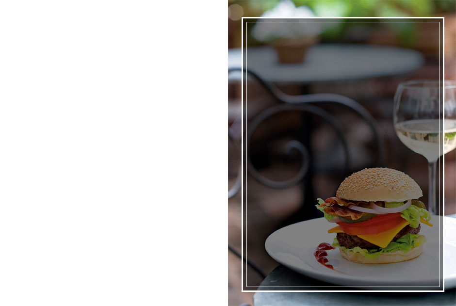 Background image of burger on white plate on outside table.