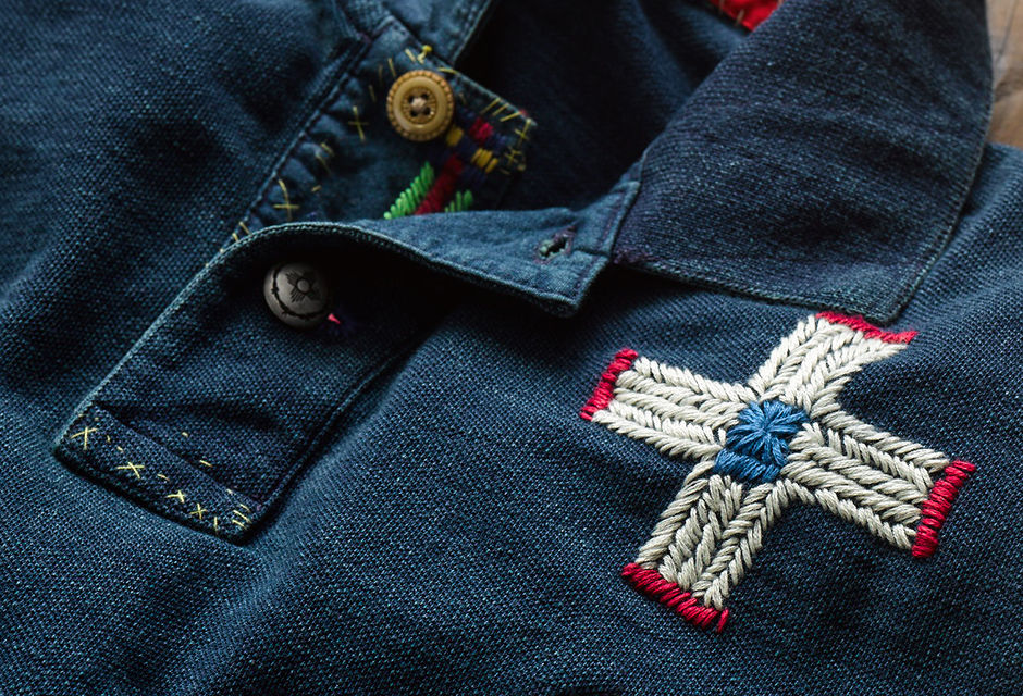 Close-up of red, white & blue cross embroidered at chest