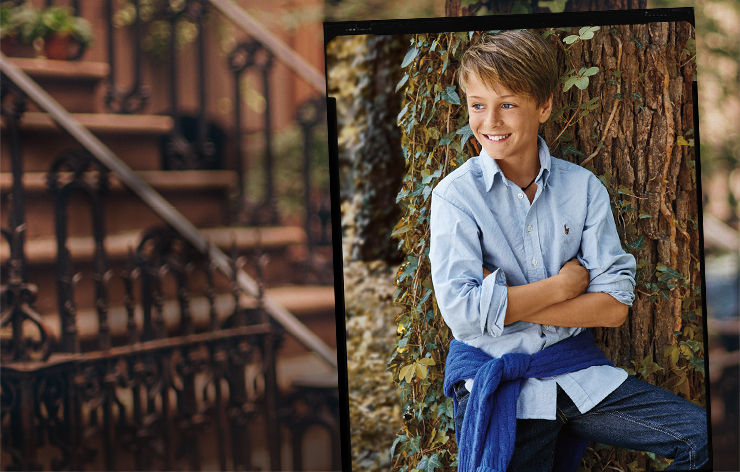 Boy wears blue button-down shirt; background of New York City brownstones.